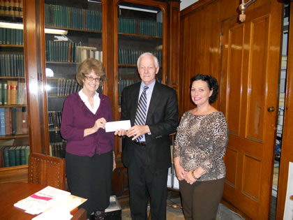 Cherry Bamberg (left) presents City Archivist Paul Campbell and City Clerk Anna Stetson with a check for $1,000.